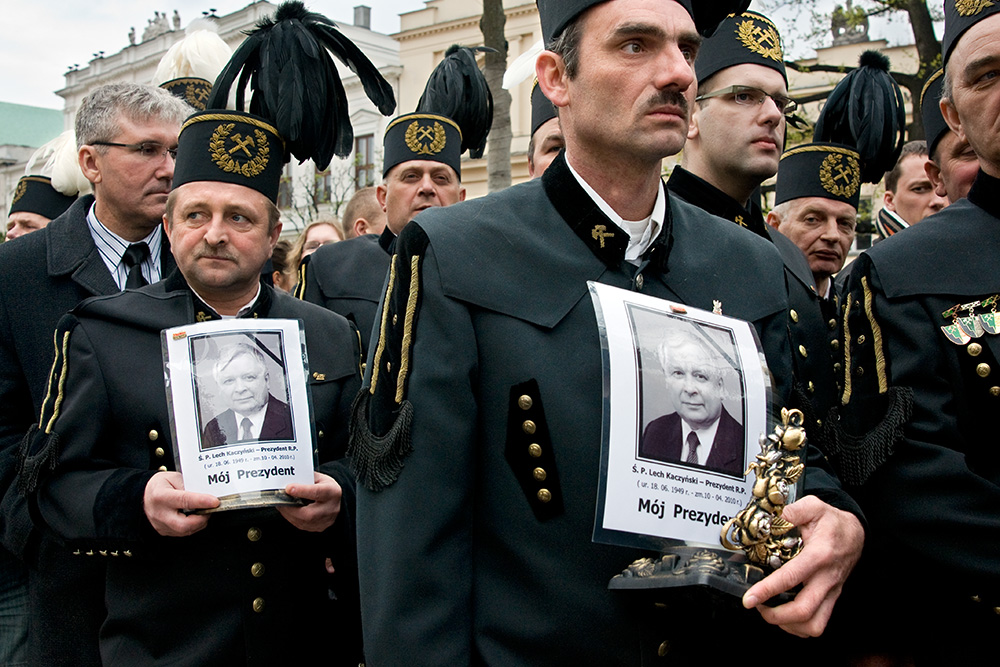 Miners came from the southern Poland wait in a queue to the Presidential Palace to place a note in a book of condolence and pay a tribute to the dead President.