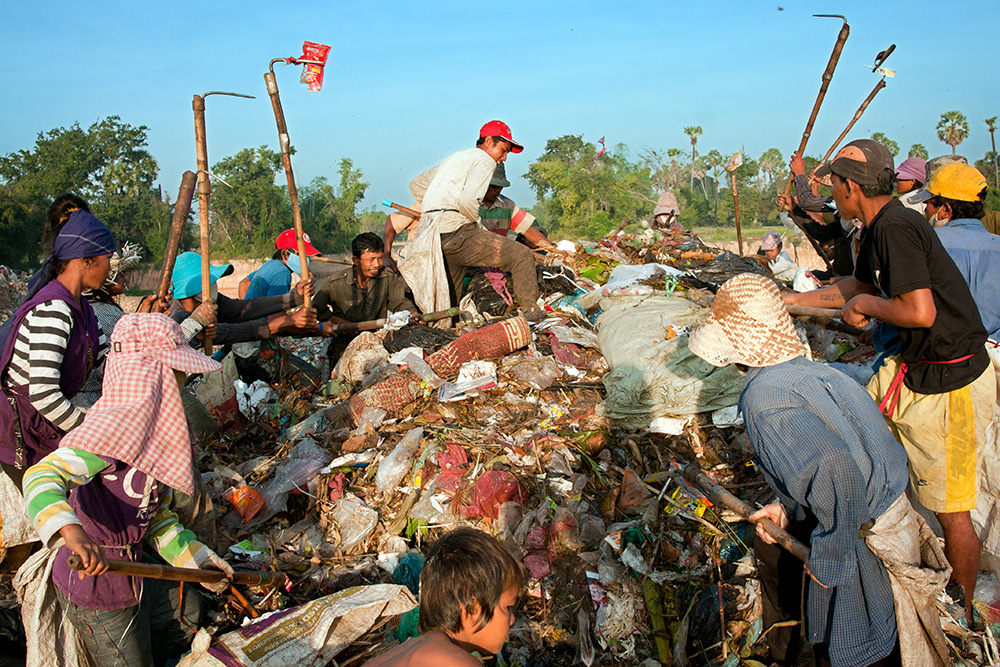 Garbage dump residents browse recently dumped waste looking for recyclable material or any other useful objects. Families compete with each other to find the most valuable items.