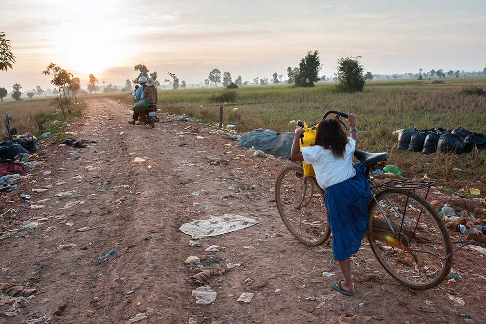 Garbage dump in Siem Reap. A girl goes to school on an adult bicycle. Only some of the inhabitants can afford to provide educations for their children. Others have to work with their parents on the dump.
