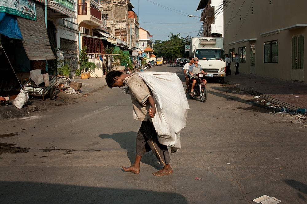 A recyclable waste collector walks in the center of Phnom Penh. Waste collectors are the poorest people in Cambodia and this job is their only way to gain any income.