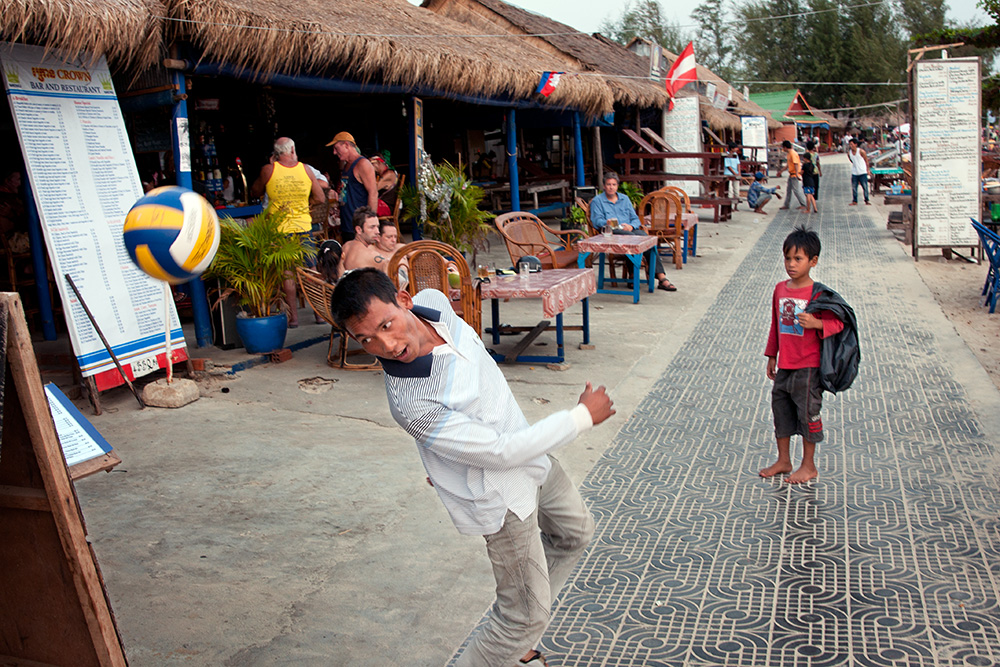 A young scavenger watch a man playing a ball. Seafront promenade in Sihanoukville, a popular tourist destination in Cambodia.