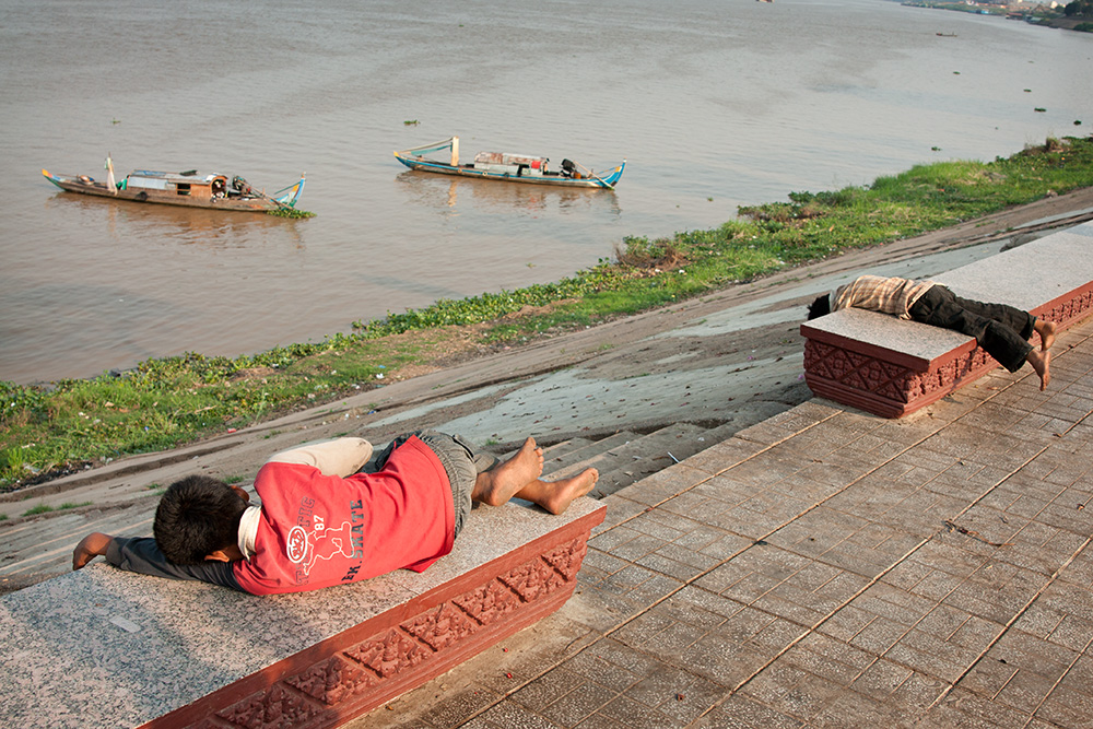 Young collectors take a nap on the riverside promenade in Phnom Penh. They scavenge the streets for useful material since early morning till very late every day.