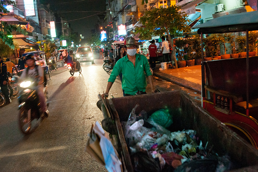A cleaning company's employee carries garbage container at night in center of Phnom Penh. All potentially valuable materials whose can be sold are already taken away by scavengers.