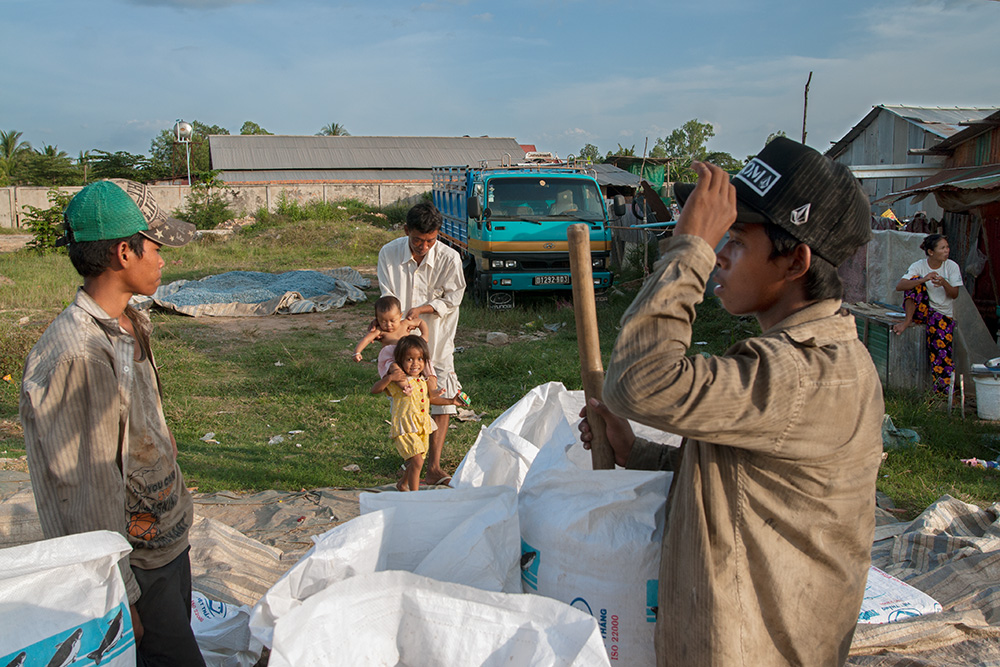 Young men load minced recycled plastic into bags for sale. A warehouse owner plays with his kids at the background.